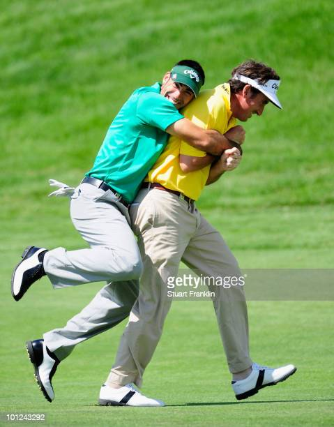 Alvaro Quiros holds onto playing partner and country man Gonzalo Fernandez Castano of Spain during the second round of the Madrid Masters at Real...