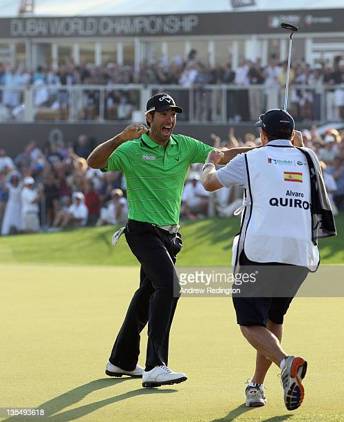 Alvaro Quiros of Spain celebrates with his caddie Michael Kerr after holing an eagle putt on the 18th green to win the Dubai World Championship on...