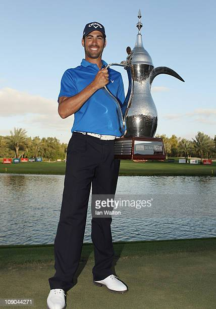 Alvaro Quiros of Spain celebrates with the trophy after winning the final round for the 2011 Omega Dubai desert Classic held on the Majilis Course at...