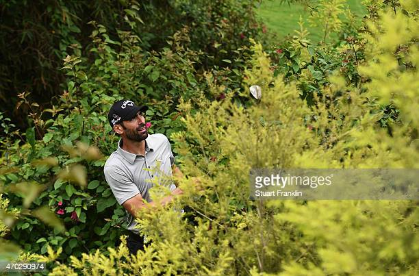 Alvaro Quiros of Spain plays a shot from the bushes on the 18th hole during the final round of the Shenzhen International at Genzon Golf Club on...