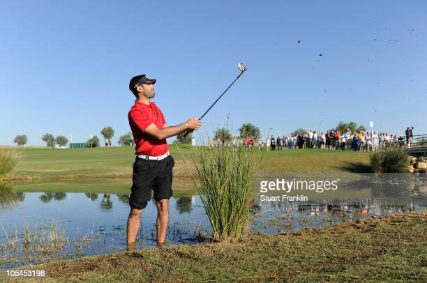 Alvaro Quiros of Spain plays his approach to the 14th green while standing in the lake during the first round of the Portugal Masters at the Oceanico...