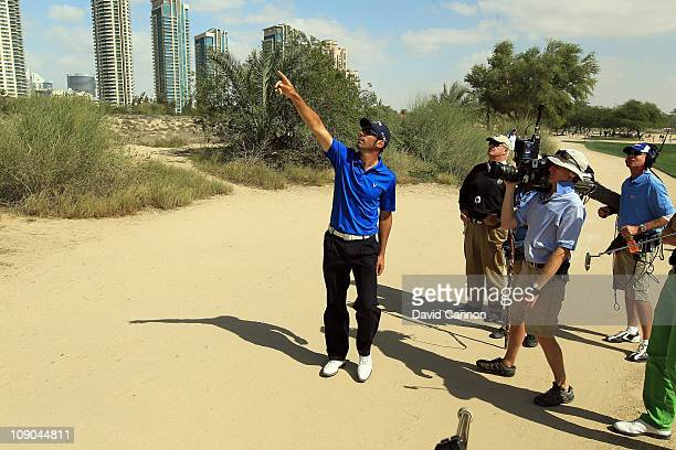 Alvaro Quiros of Spain searches for his ball that was stuck up a palm tree after his third shot with the help of tournament referee John Paramor at...