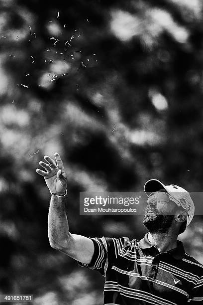 Alvaro Quiros of Spain throws grass in the air to judge the wind direction before he hits his second shot on the 10th hole during Day 2 of the Open...