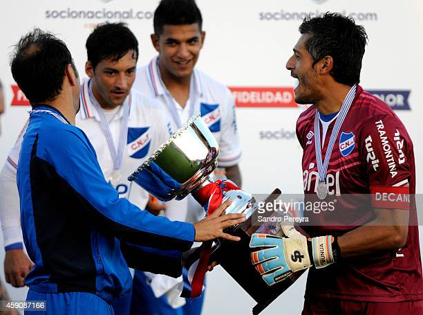 Alvaro Recoba, Gonzalo Porras, Diego Polenta and Gustavo Munua of Nacional lift the trophy after winning a match between Cerro and Nacional as part...
