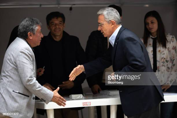 Alvaro Uribe former president of Colombia center extends his hand to a polling official while arriving to cast his ballot at the National Congress...