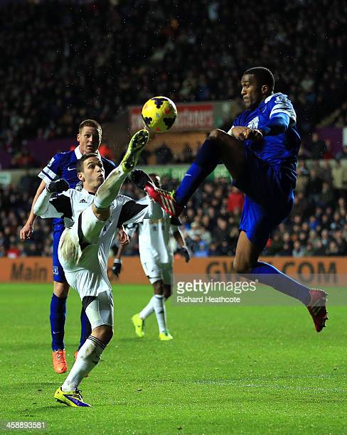 Alvaro Vazquez of Swansea and Sylvain Distin of Everton compete for the ball during the Barclays Premier League match between Swansea City and...