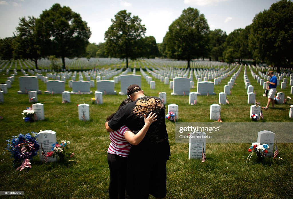 Alvin Amezquite and his wife Erika Amezquita of New York City embrace at the grave of their friend U.S. Army Staff Sgt. Christian Philip Engeldrum on Memorial Day in Section 60 of Arlington National Cemetery May 31, 2010 in Arlington, Virginia. Amezquite and Engeldrum served together in the National Guard and were friends for more than 12 years. This is the 142nd Memorial Day observance at the cemetery.