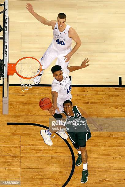 Alvin Ellis III of the Michigan State Spartans drives to the basket against Jahlil Okafor and Marshall Plumlee of the Duke Blue Devils in the first...