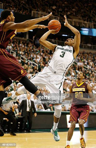 Alvin Ellis III of the Michigan State Spartans tries to get a second half shot off over Maurice Walker of the Minnesota Golden Gophers at the Jack T...
