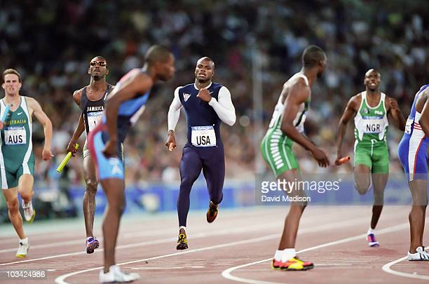 Alvin Harrison of the US approaches the exchange zone to handoff to his teammate Antonio Pettigrew during the final of the Men's 4x400m Relay event...