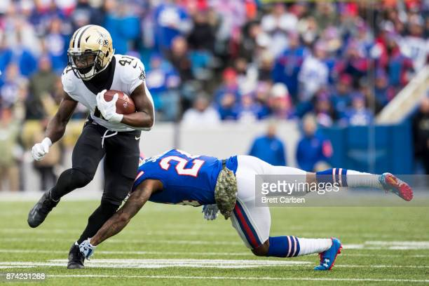 Alvin Kamara of the New Orleans Saints carries the ball as Leonard Johnson of the Buffalo Bills dives attempting to tackle during the first quarter...