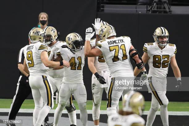 Alvin Kamara of the New Orleans Saints celebrates with Drew Brees and Ryan Ramczyk after scoring a touchdown during the first quarter against the Las...
