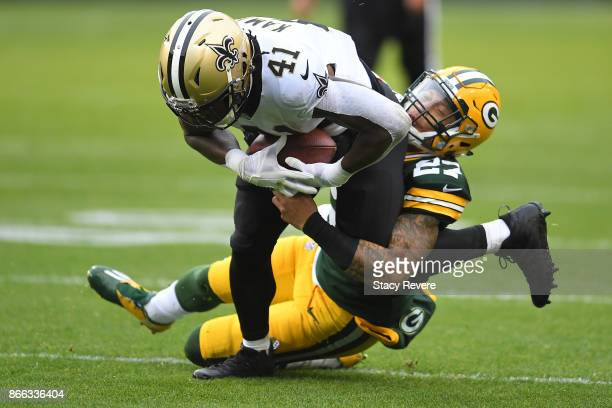 Alvin Kamara of the New Orleans Saints is brought down by Josh Jones of the Green Bay Packers during a game at Lambeau Field on October 22 2017 in...