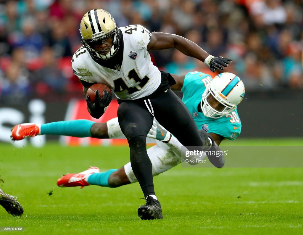 Alvin Kamara of the New Orleans Saints is challenged by Cordrea Tankersley of Miami Dolphins during the NFL match between New Orleans Saints and Miami Dolphins at Wembley Stadium on October 1, 2017 in London, England.