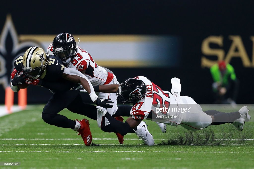 Alvin Kamara #41 of the New Orleans Saints is tackled by Damontae Kazee #27 of the Atlanta Falcons and LaRoy Reynolds #53 during the second half of a game at the Mercedes-Benz Superdome on December 24, 2017 in New Orleans, Louisiana.