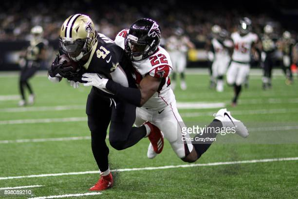 Alvin Kamara of the New Orleans Saints is tackled by Keanu Neal of the Atlanta Falcons at MercedesBenz Superdome on December 24 2017 in New Orleans...
