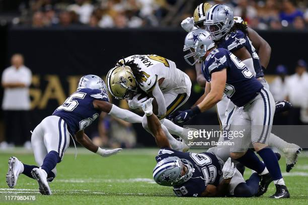 Alvin Kamara of the New Orleans Saints is tackled by Xavier Woods of the Dallas Cowboys and Robert Quinn during the second half of a game at the...