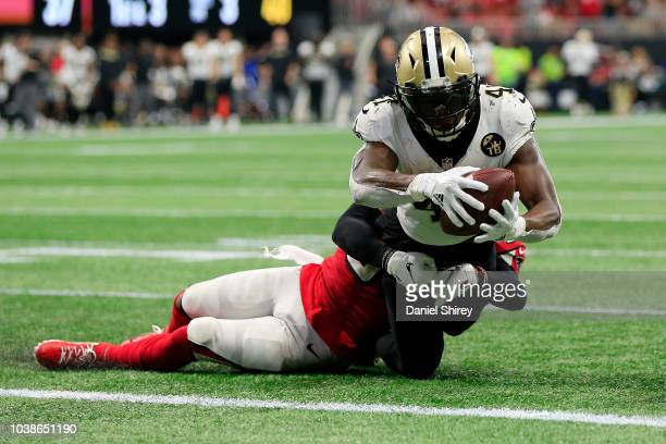 Alvin Kamara of the New Orleans Saints is tackled short of a touchdown by Brian Poole of the Atlanta Falcons during overtime at Mercedes-Benz Stadium...