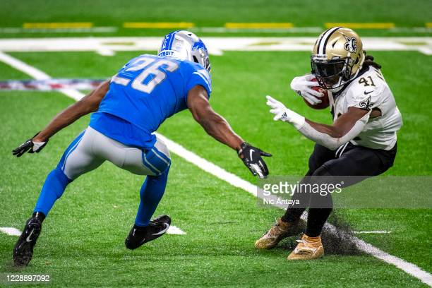 Alvin Kamara of the New Orleans Saints jukes Duron Harmon of the Detroit Lions during the fourth quarter at Ford Field on October 4, 2020 in Detroit,...