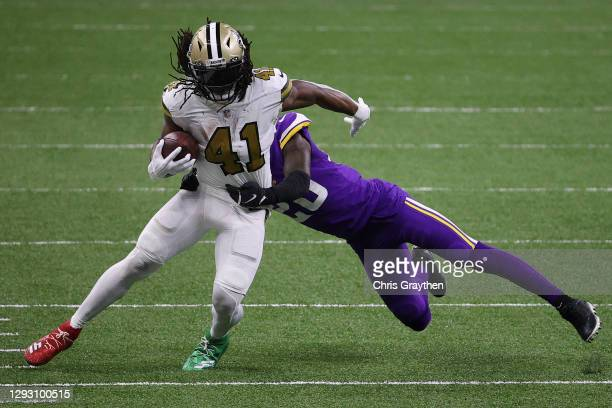 Alvin Kamara of the New Orleans Saints makes a reception past Jeff Gladney of the Minnesota Vikings during the fourth quarter at Mercedes-Benz...