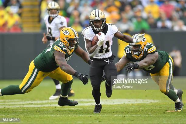 Alvin Kamara of the New Orleans Saints runs between Kenny Clark and Mike Daniels of the Green Bay Packers during the second half at Lambeau Field on...