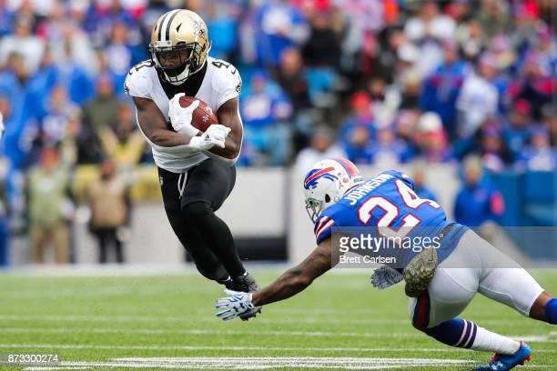 Alvin Kamara of the New Orleans Saints runs the ball as Leonard Johnson of the Buffalo Bills attempts to tackle him during the first quarter on...