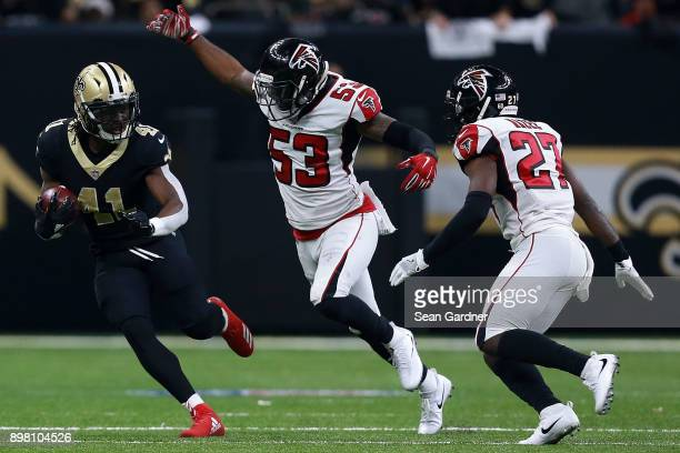 Alvin Kamara of the New Orleans Saints runs with the ball as Damontae Kazee of the Atlanta Falcons and LaRoy Reynolds defend during the second half...