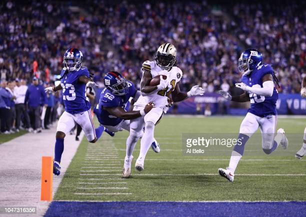 Alvin Kamara of the New Orleans Saints scores a touchdown aa Alec Ogletree of the New York Giants during their game at MetLife Stadium on September...