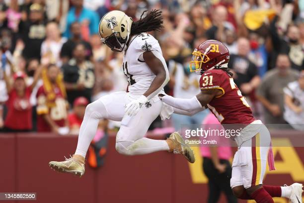 Alvin Kamara of the New Orleans Saints scores a touchdown as Kamren Curl of the Washington Football Team defends during the first half at FedExField...
