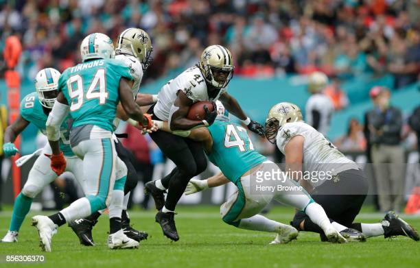 Alvin Kamara of the New Orleans Saints tackled by Kiko Alonso of the Miami Dolphins during the NFL game between the Miami Dolphins and the New...
