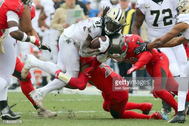 Alvin Kamara of the Saints is brought down by two Bucs defenders during the regular season game between the New Orleans Saints and the Tampa Bay...