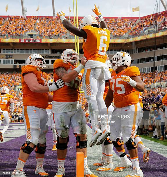 Alvin Kamara of the Tennessee Volunteers is lifted by teammates after scoring a touchdown against the Northwestern Wildcats during the first half of...