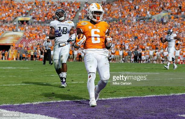 Alvin Kamara of the Tennessee Volunteers scores a touchdown as Anthony Walker of the Northwestern Wildcats reacts during the first half of the...