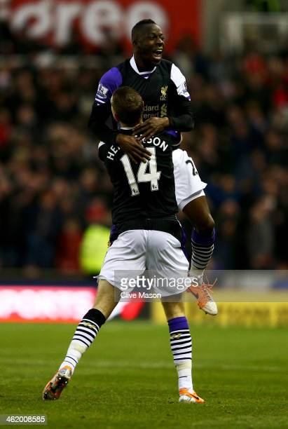 Aly Cissokho of Liverpool celebrates with Jordan Henderson as his shot deflects in off Ryan Shawcross of Stoke City for an own goal for their first...
