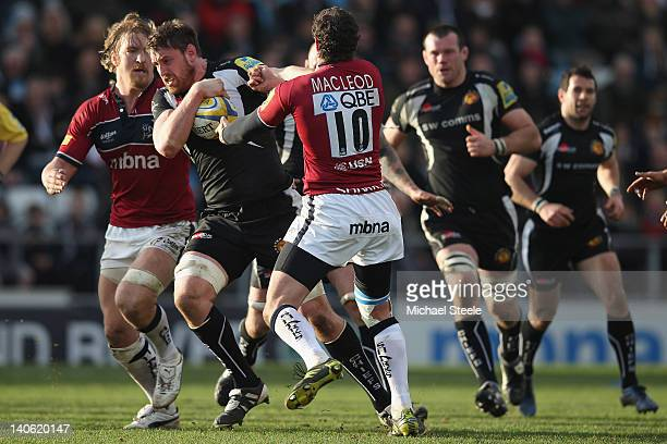 Aly Muldowney of Exeter Chiefs bursts through the challenge of Nick McLeod and Andy Powell of Sale Sharks during the Aviva Premiership match between...