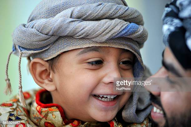 Alyan Khan 36 yrs old smiles along with his father after offer ritual morning prayers during celebration of Eid alFitr on July 7 2016 in Kashmire...