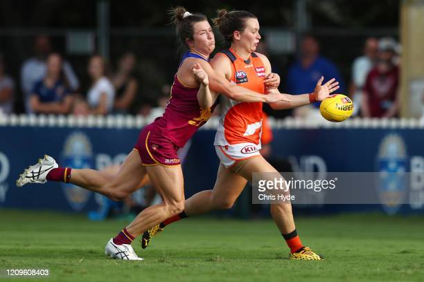 Alyce Parker of the Giants kicks while tackled by Catherine Svarc of the Lions during the round four AFLW match between the Brisbane Lions and the...