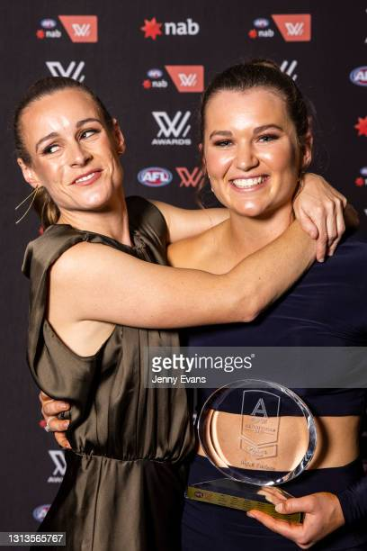 Alyce Parker of the GWS Giants holds her AFLW All Australian award as she is hugged by Alicia Eva during the 2021 AFLW W Awards at Sydney Cricket...