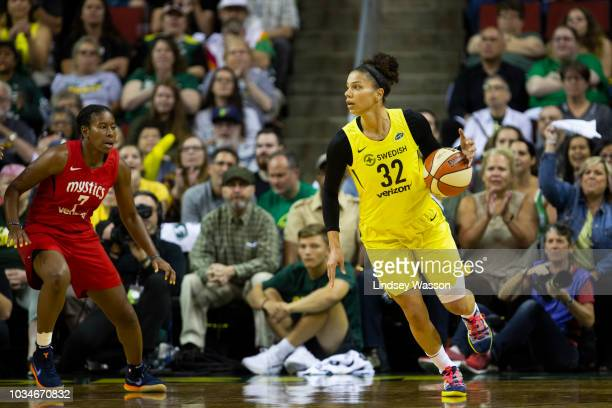 Alysha Clark of the Seattle Storm looks for an opening around Ariel Atkins of the Washington Mystics during the first half of Game 2 of the WNBA...