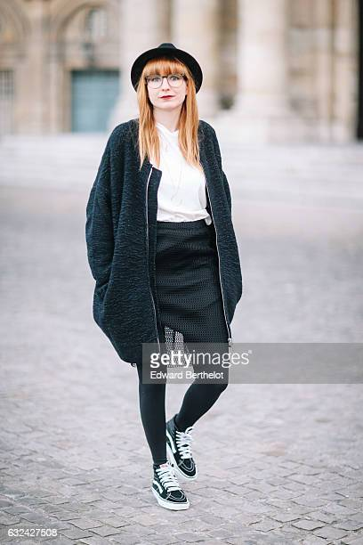 Alyson Marion is wearing a black hat, a black cape, a white top, a black dress, black tights, and black shoes, during Paris Fashion Week Menswear...