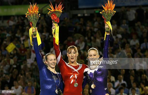 Alyssa Brown of Canada Imogen Cairns of England and Naomi Russell of Australia wave to the crowd after receiving their medals during the Artistic...