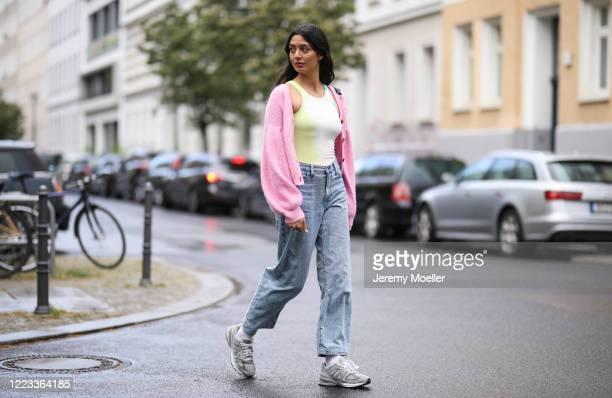Alyssa Cordes wearing New Balance sneaker, Baum & Pferdgarten cardigan, Levis jeans and Weekday top on May 05, 2020 in Berlin, Germany.