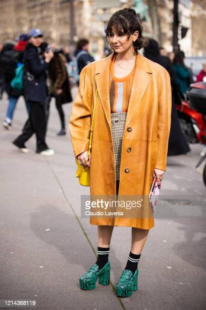 Alyssa Coscarelli, wearing an orange striped sweater, beige checked shorts, tan leather coat, yellow bag and green snakeskin print heels, is seen...