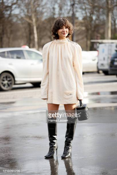 Alyssa Coscarelli wearing Chanel ivory dress black Chanel bag and black boots outside the Chanel show during Paris Fashion Week Womenswear...