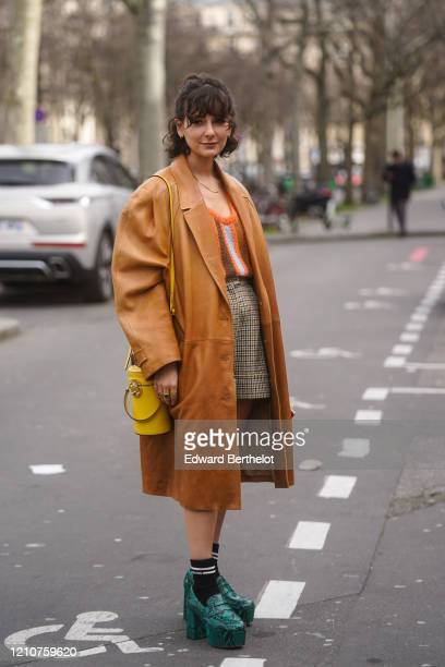 Alyssa Coscarelli wears an oversized leather long coat, a yellow bag, a striped pullover, a checked skirt, Miu Miu socks, green snake pattern shoes,...