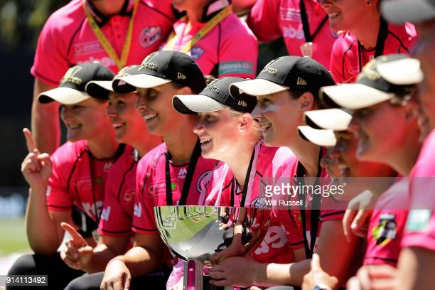 Alyssa Healy and Ellyse Perry of the Sixers pose with the trophy after winning during the Big Bash League Final match between the Adelaide Strikers...