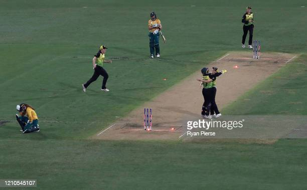 Alyssa Healy and Megan Schutt of Australia celebrate victory as Laura Wolvaardt and Nadine De Klerk of South Africa look dejected during the ICC...