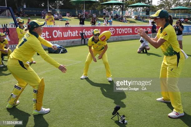 Alyssa Healy of Australia plays Aussie Rules football with Megan Schutt and Georgia Wareham of Australia during game three of the One Day...