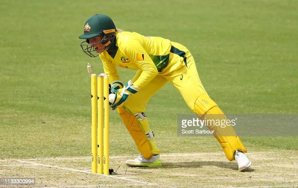 Alyssa Healy of Australia runs out Katie Perkins of New Zealand during game three of the One Day International Series between Australia and New...