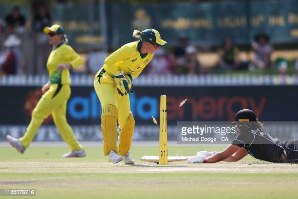 Alyssa Healy of Australia tries to run out Suzie Bates of New Zealand bats during game three of the One Day International Series between Australia...
